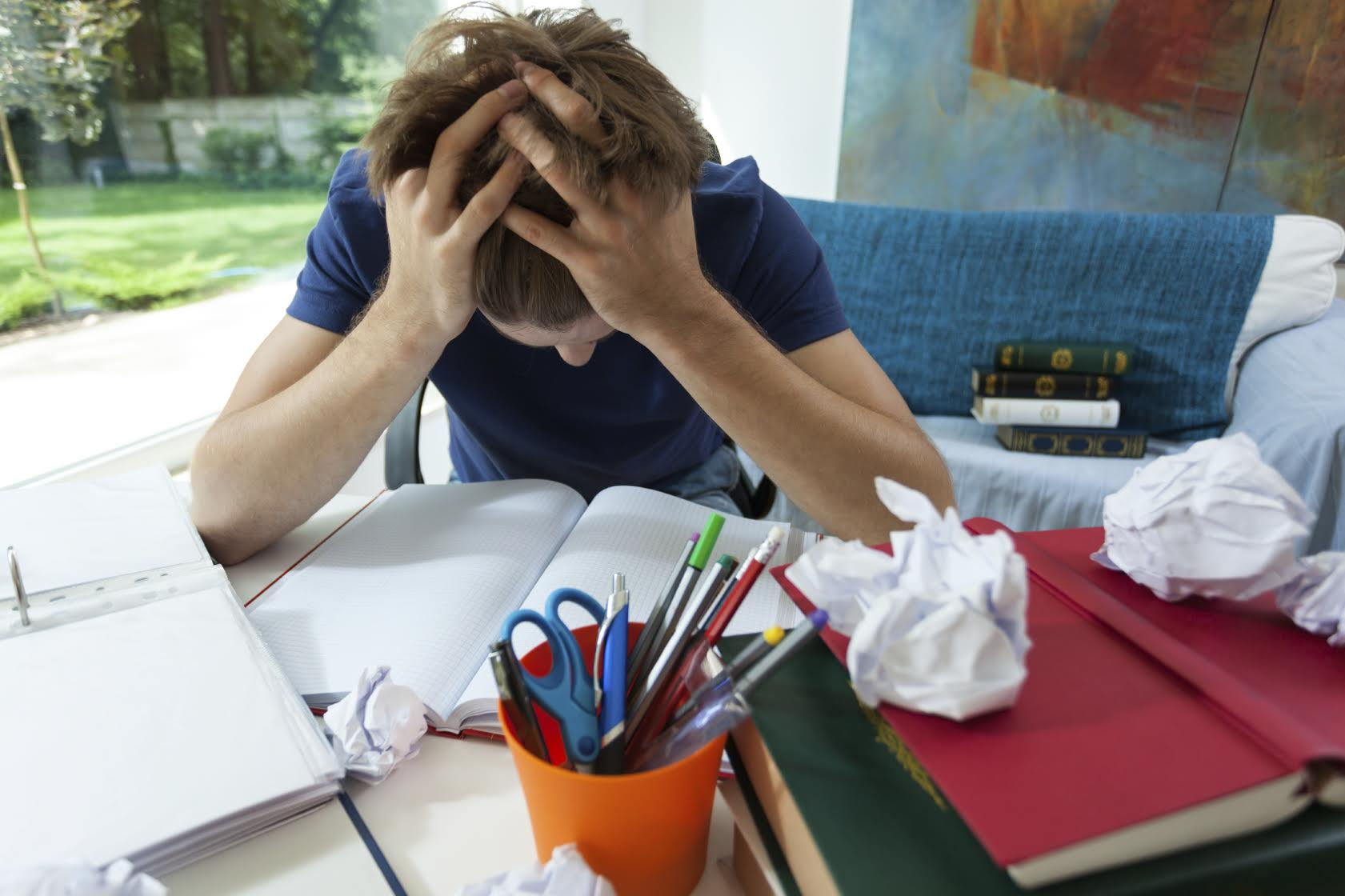 Exhausted student in blue t-shirt learning at home